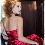Seated girl in red satin dress turns to over her shoulder and show off beautifu occaision hair by pHd Malvern
